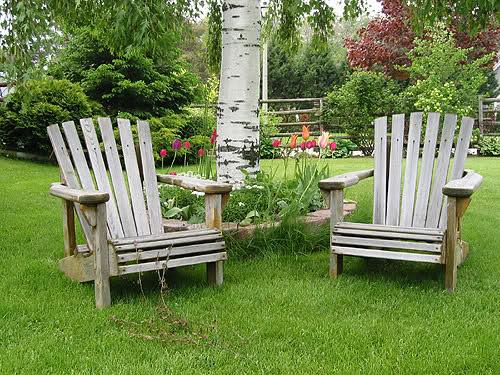 Eleganckie krzesła ogrodowe wykonane z drewna stanowią idealny element ozdobny naszego ogródka.